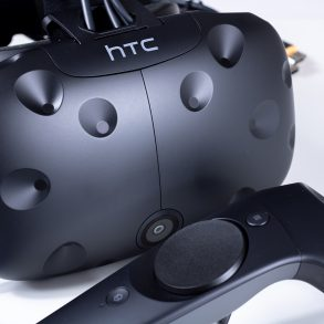 HTC Vive VR headset with controller in front of it.