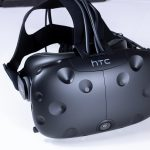Front angled view of the HTC Vive with cables and head-strap.